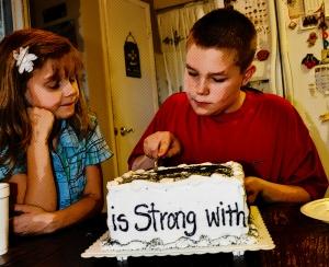 Donovan cutting his birthday cake under the watchful eyes of Ariyanna.